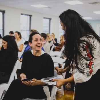 Women talking at event, sitting